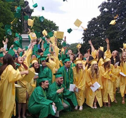 Spotlights Students tossing their hats during a graduation ceremony